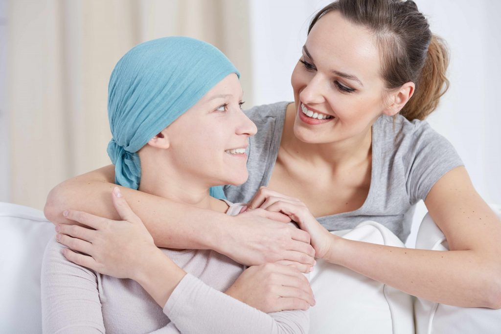two young women embracing and smiling at one another, one with a scarf on her head