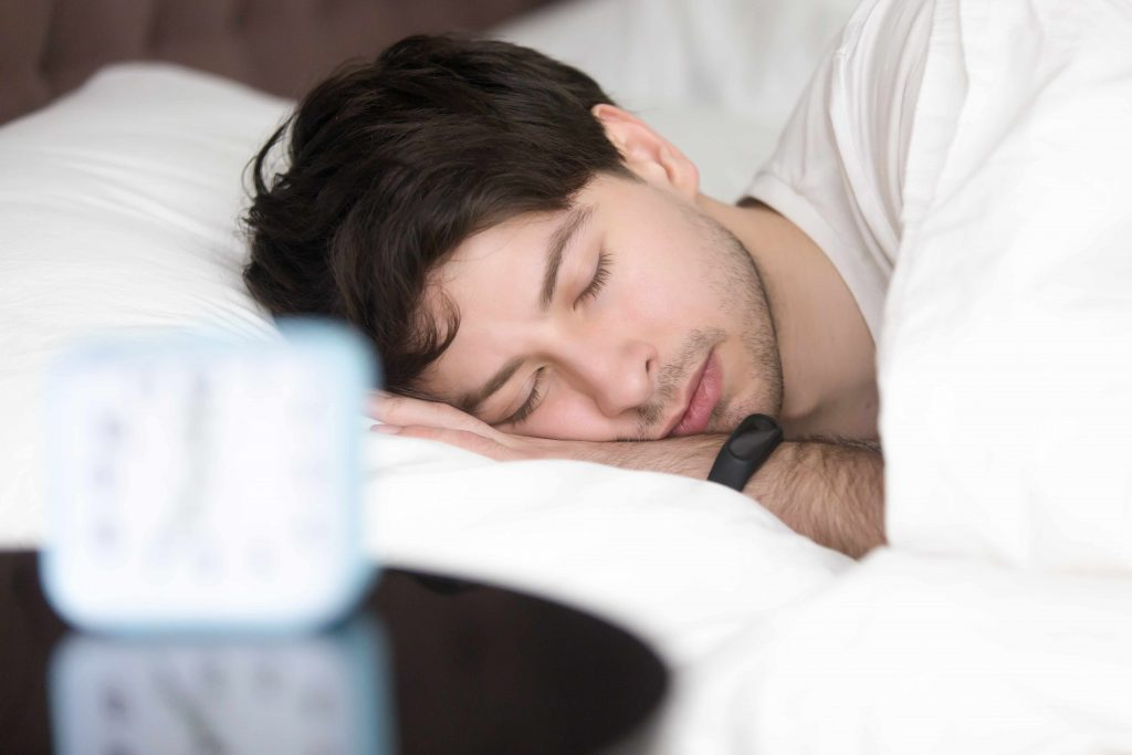 a man asleep in bed, with a fitness tracker on his wrist