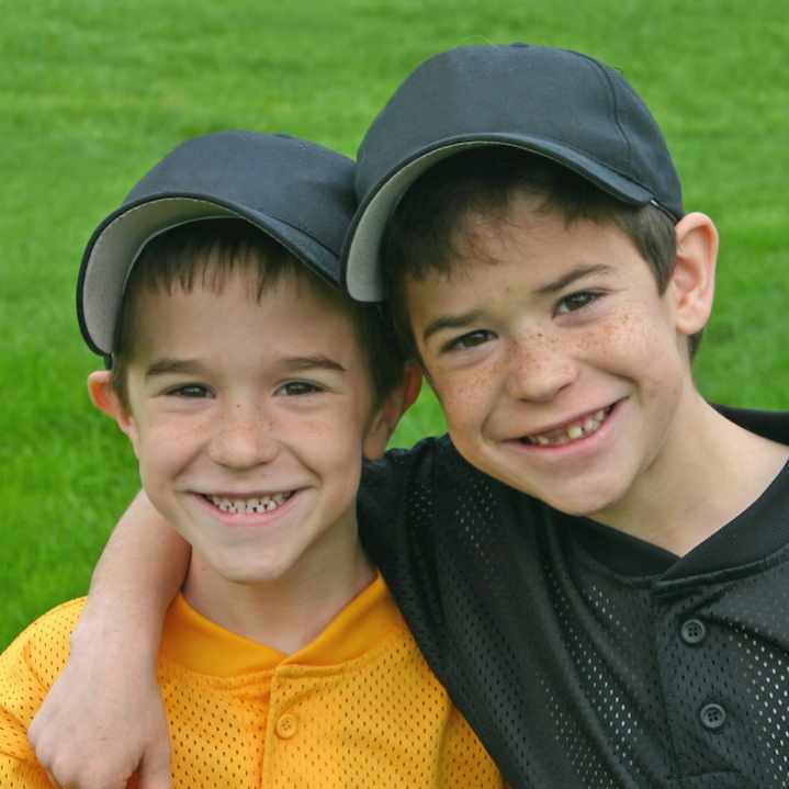 two little boys on a sports field wearing baseball caps