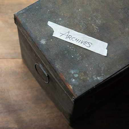 an old metal filing box for documents with a piece of tape that says 'Archives'