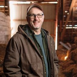 Dr. Allen Dietz standing in a barn on a farm