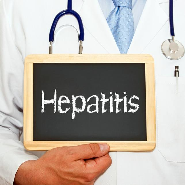 health care worker holding a blackboard on which the word hepatitis is written