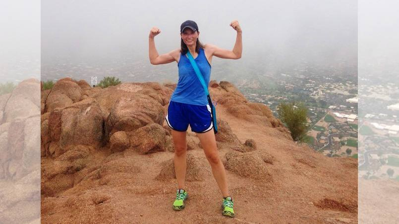 In the Loop lung disease patient Angela Tewksbury outside on a hilltop holding up her arms in triumph