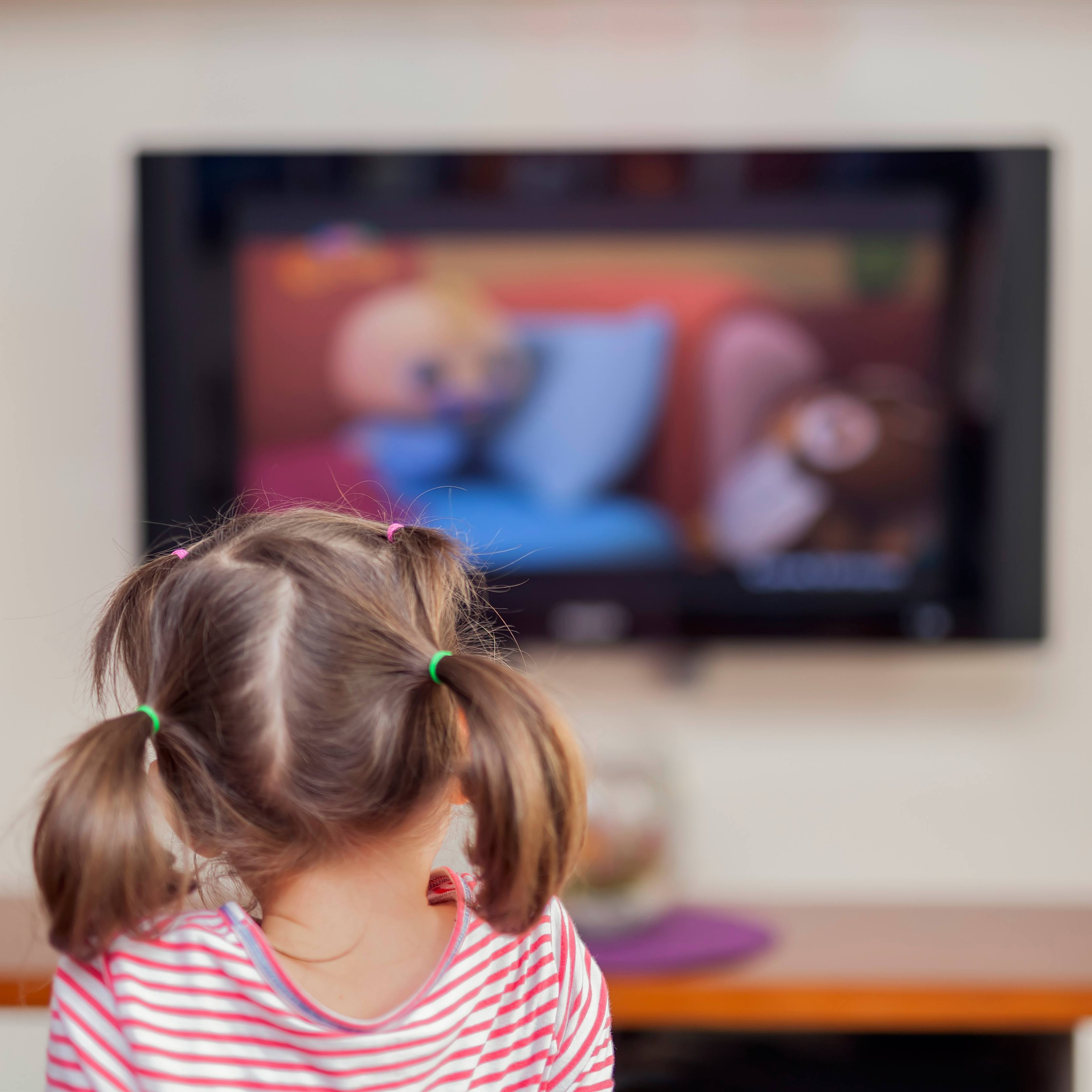 a little girl sitting in front of a TV screen