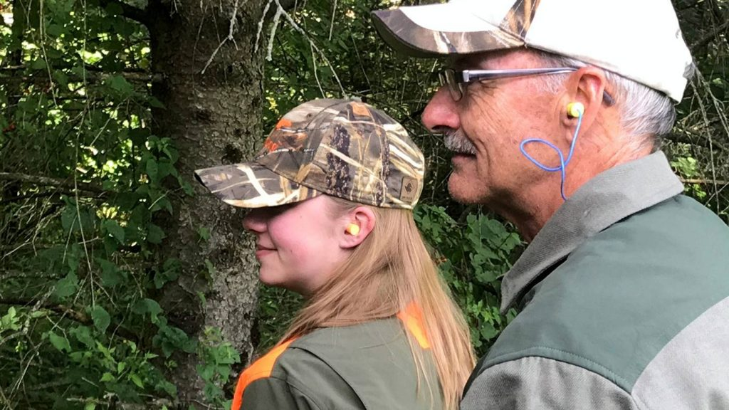 a woman and a man in hunting gear wearing ear plugs