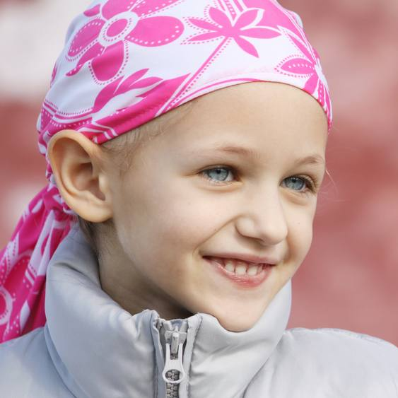 young girl with cancer wearing a bandana and smiling