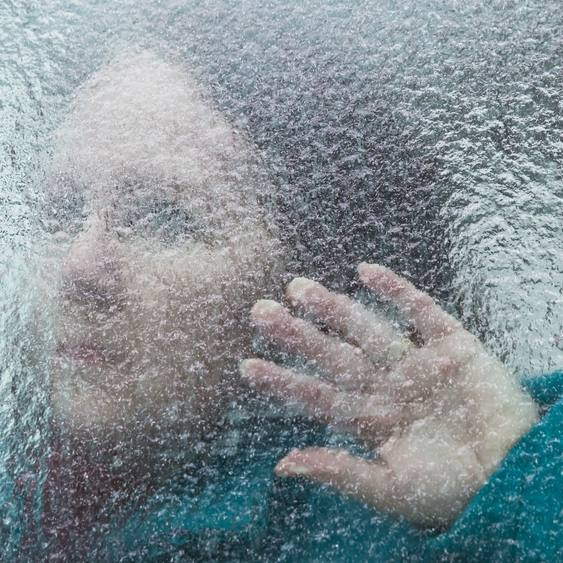 woman looking through window covered in ice