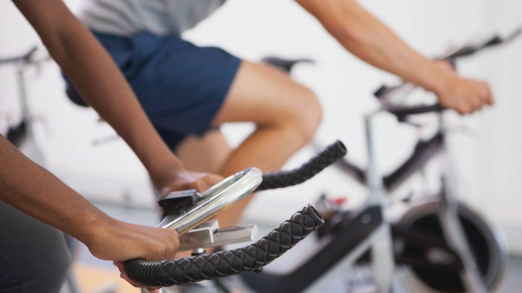 Dos hombres hacen ejercicio en bicicletas