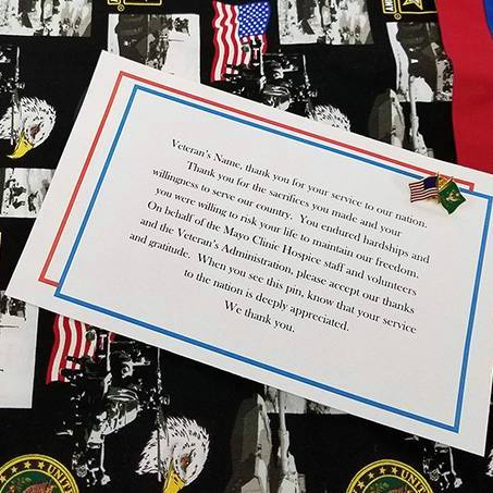 Veteran pinning items on a black cloth with a thank you note