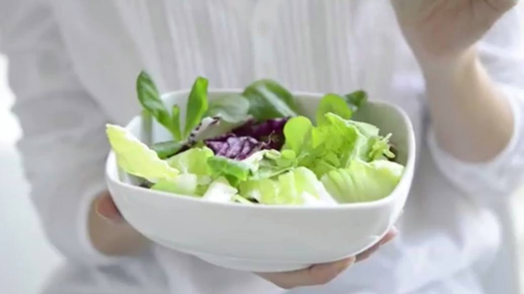 a person holding a fresh green vegetable salad in a white bowl