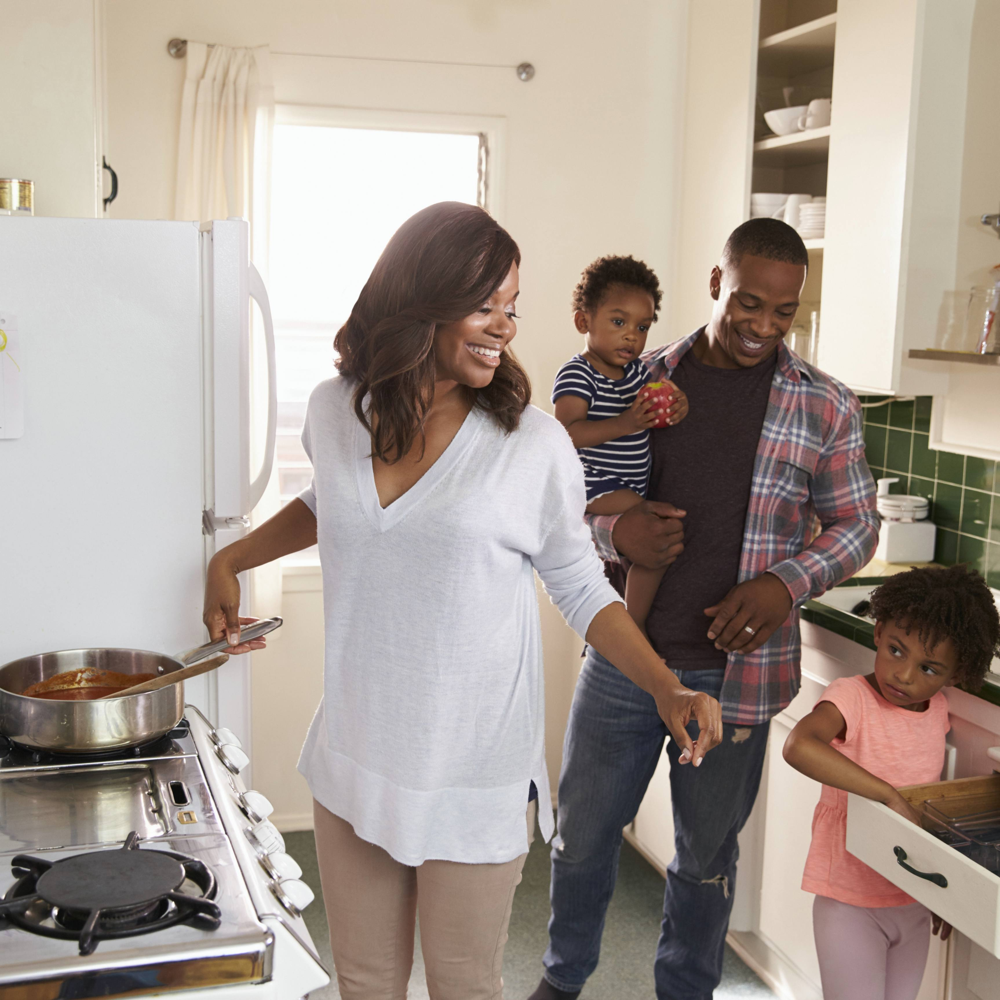 an African-American couple with children in the kitchen and cooking together