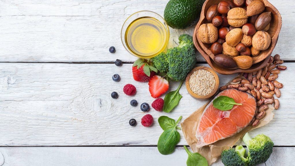 an assortment of foods included in a diabetes diet - fruits and vegetables, fish, nuts, legumes, whole grain - on a white wooden surface