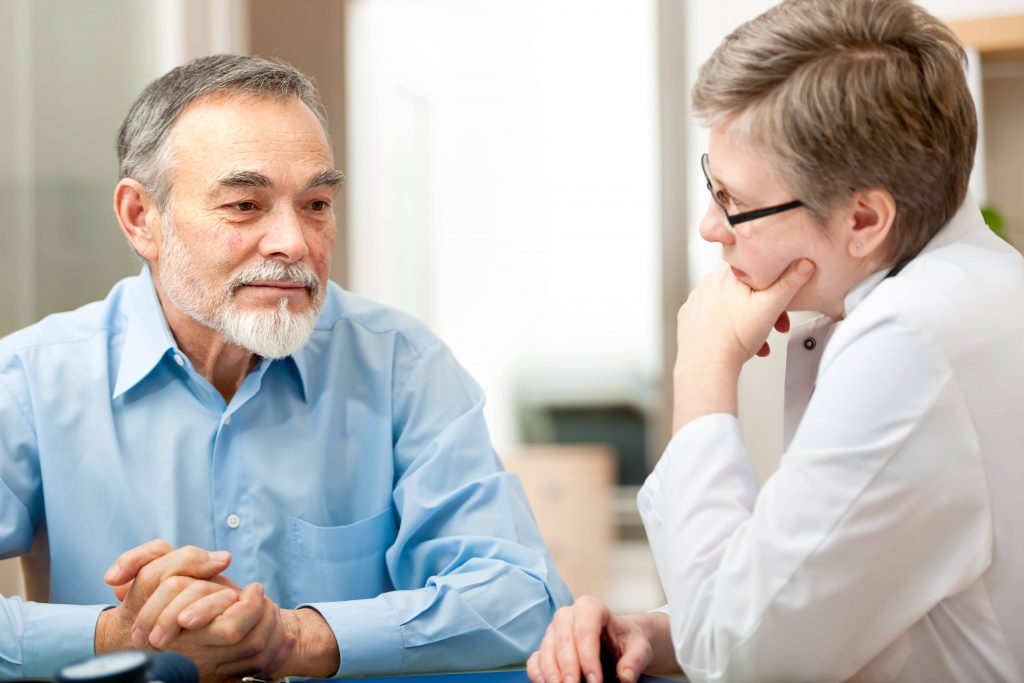 an older man, looking worried or thoughtful, talking with a female health care provider