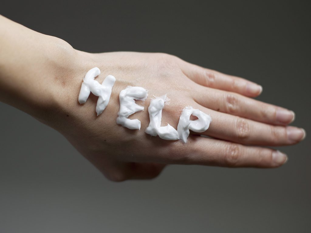 a close-up of the back of a woman's hand with the word help written in lotion