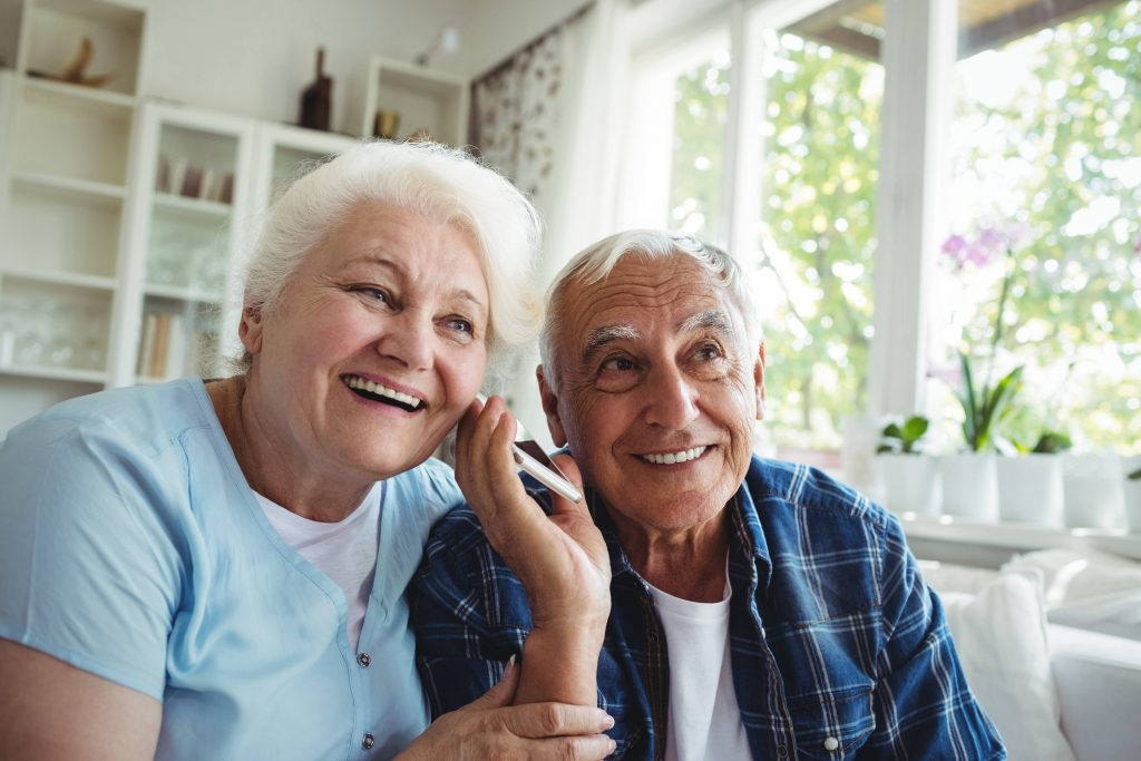 an older man and woman smiling and listening together to a cell phone