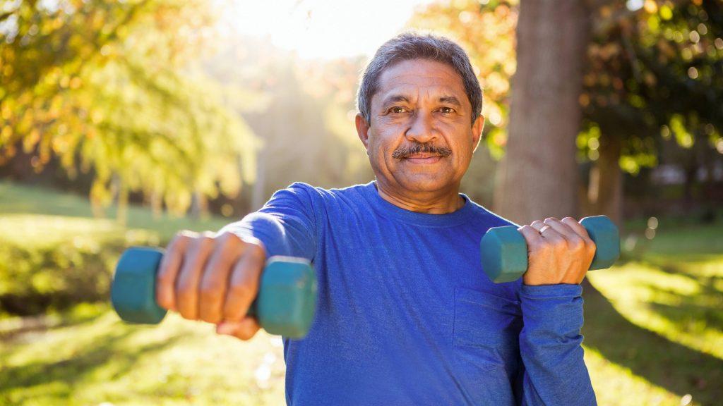 Retrato de un hombre maduro haciendo ejercicios con pesas en el parque