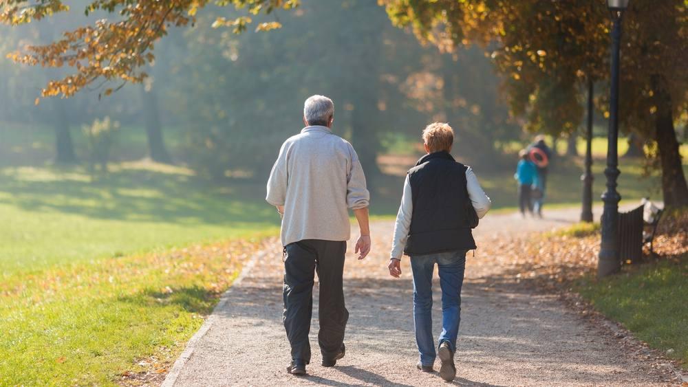 Una pareja de ancianos pasea por el parque una mañana de otoño