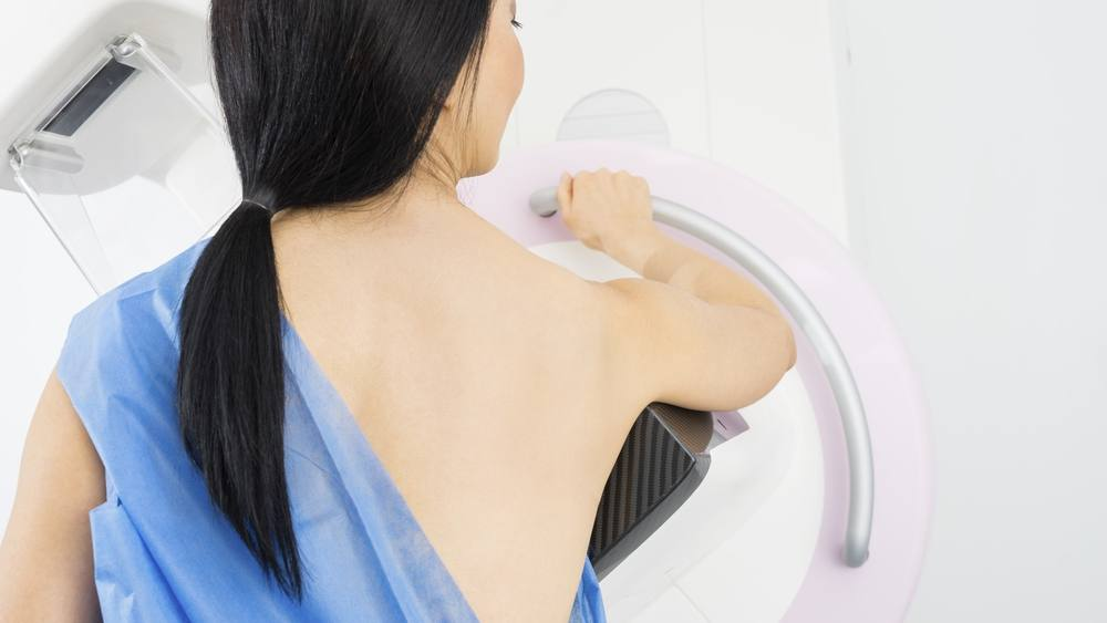 Mujer de pie frente a la máquina de mamografía
