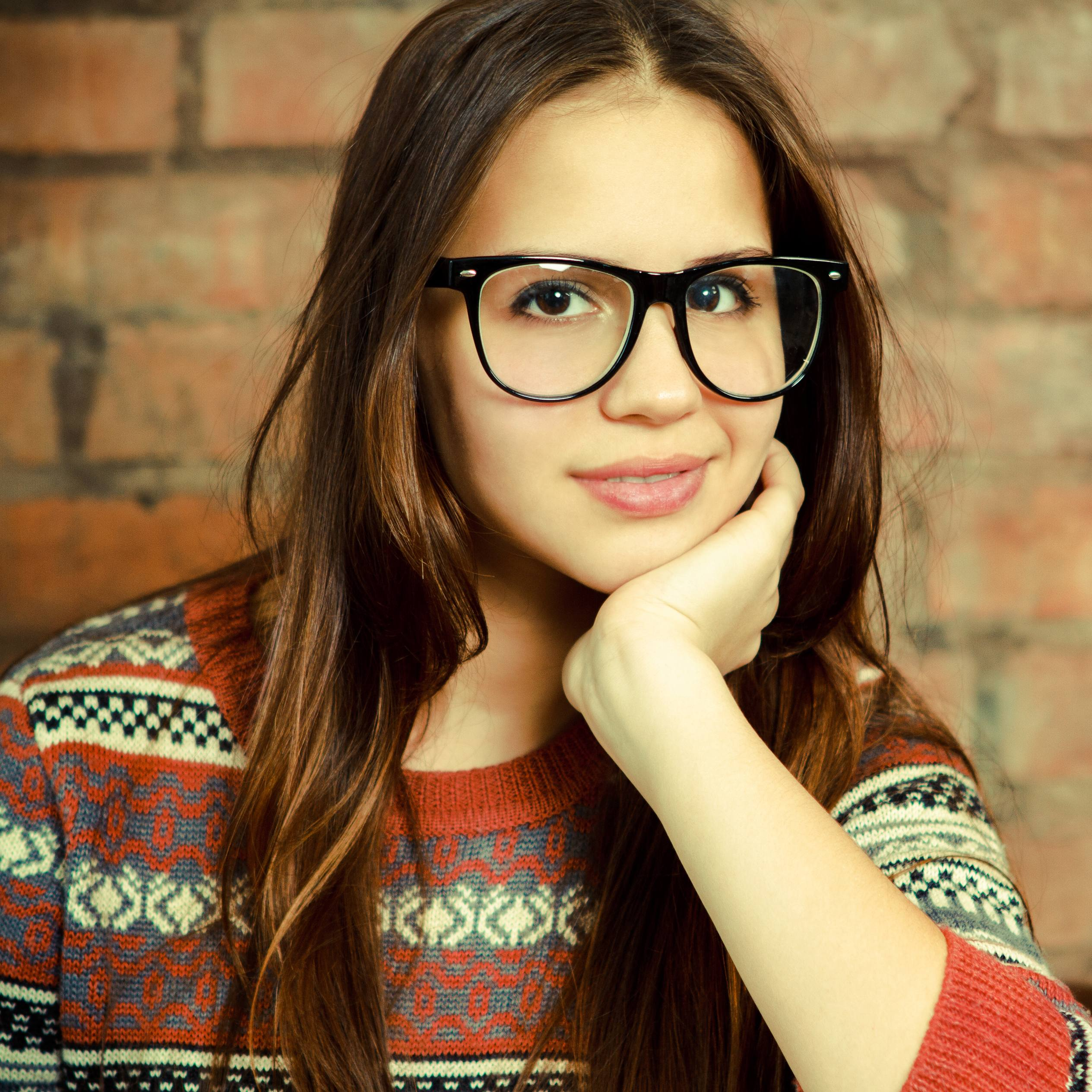 a close-up of a smiling teenage girl wearing large glasses