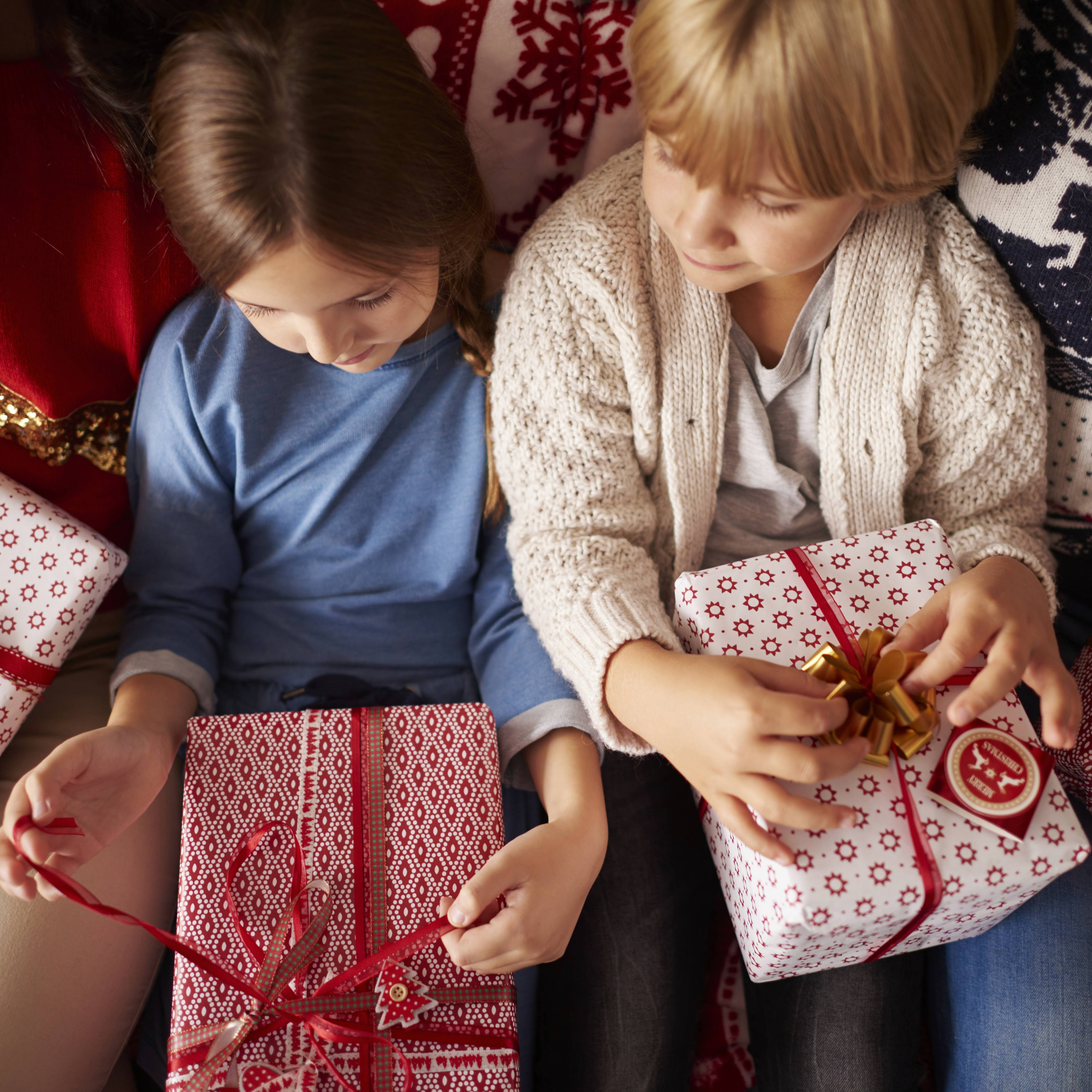 a couple of children opening family Christmas presents and gifts