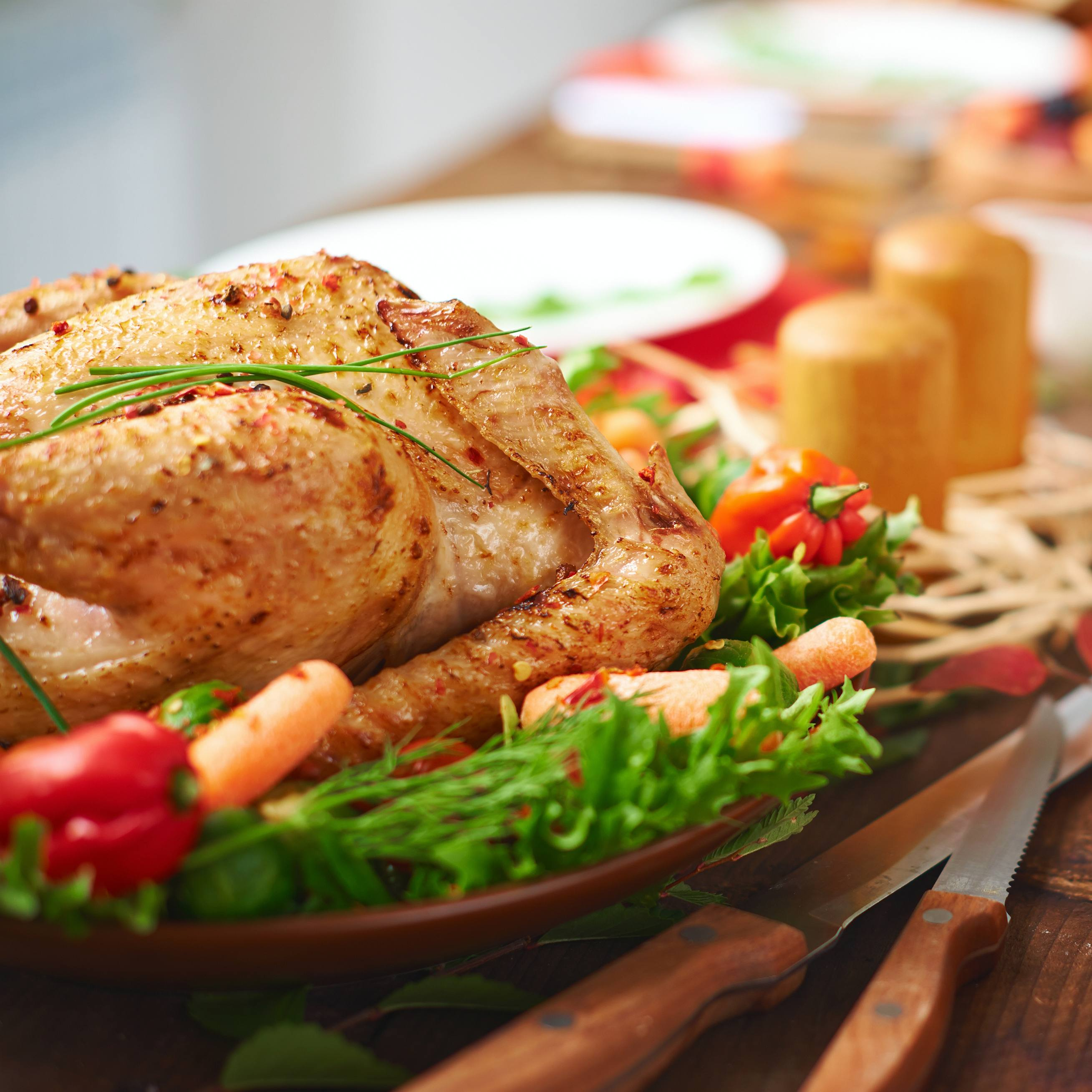 a festive holiday table with turkey, fresh vegetables