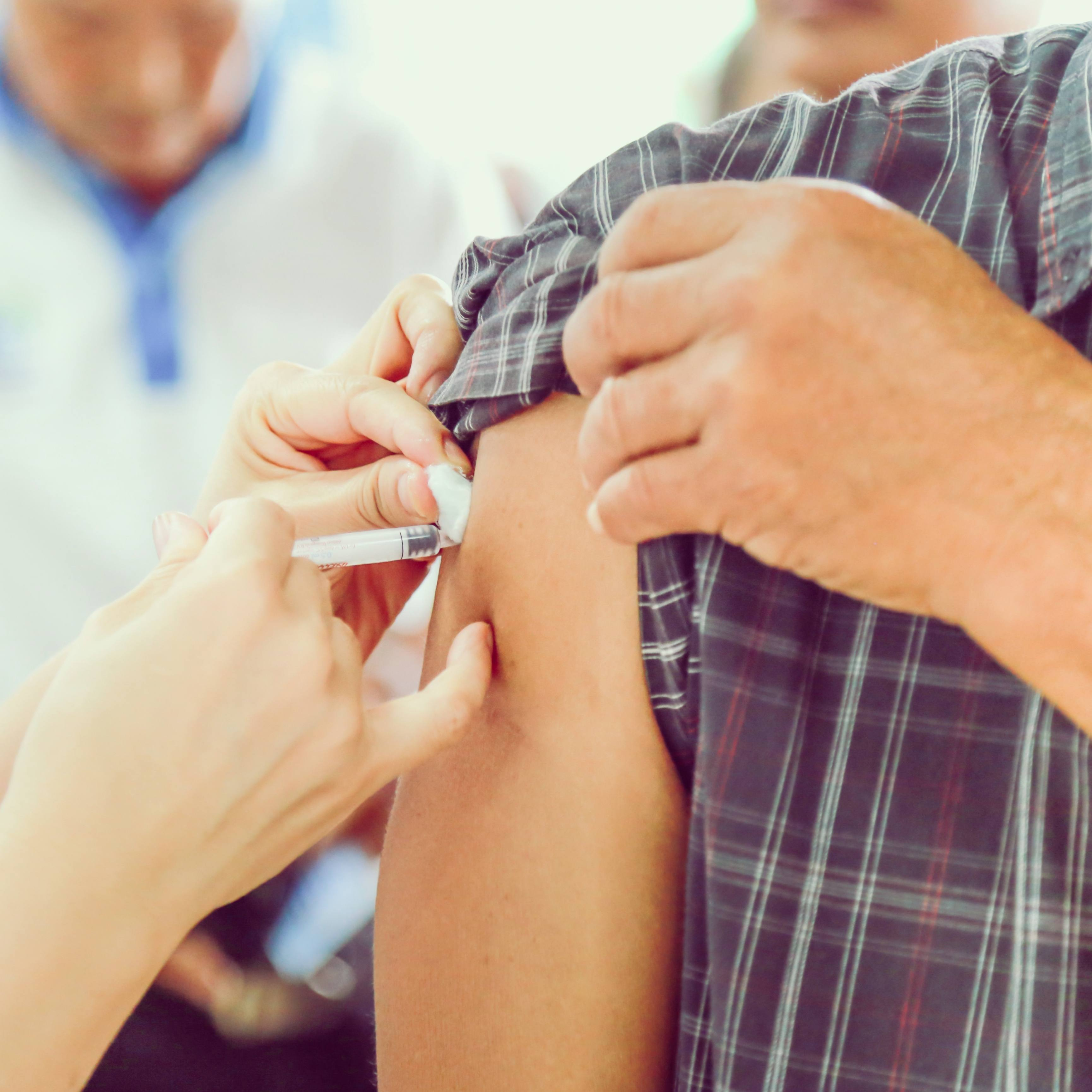 a person getting vaccinated by a healthcare person giving a flu shot
