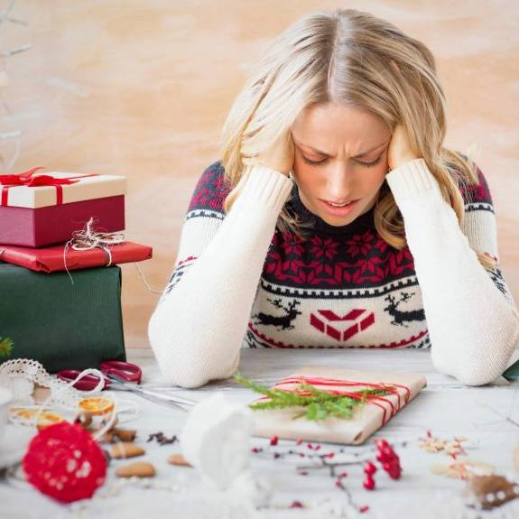 a woman tired and stressed during the holidays, holding her head in her hands with presents and wrapping paper everywhere
