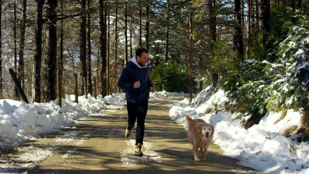 a young man exercising and running with is dog down a dirt path with snow along the road in winter