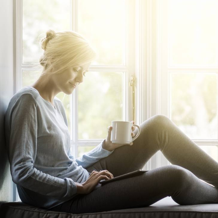 adult woman relaxing in window seat while drinking coffee