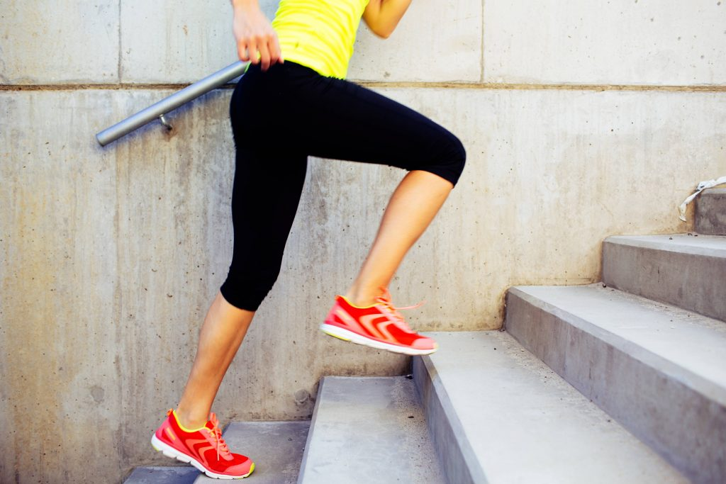 the legs and feet of a woman running up stairs, doing interval training