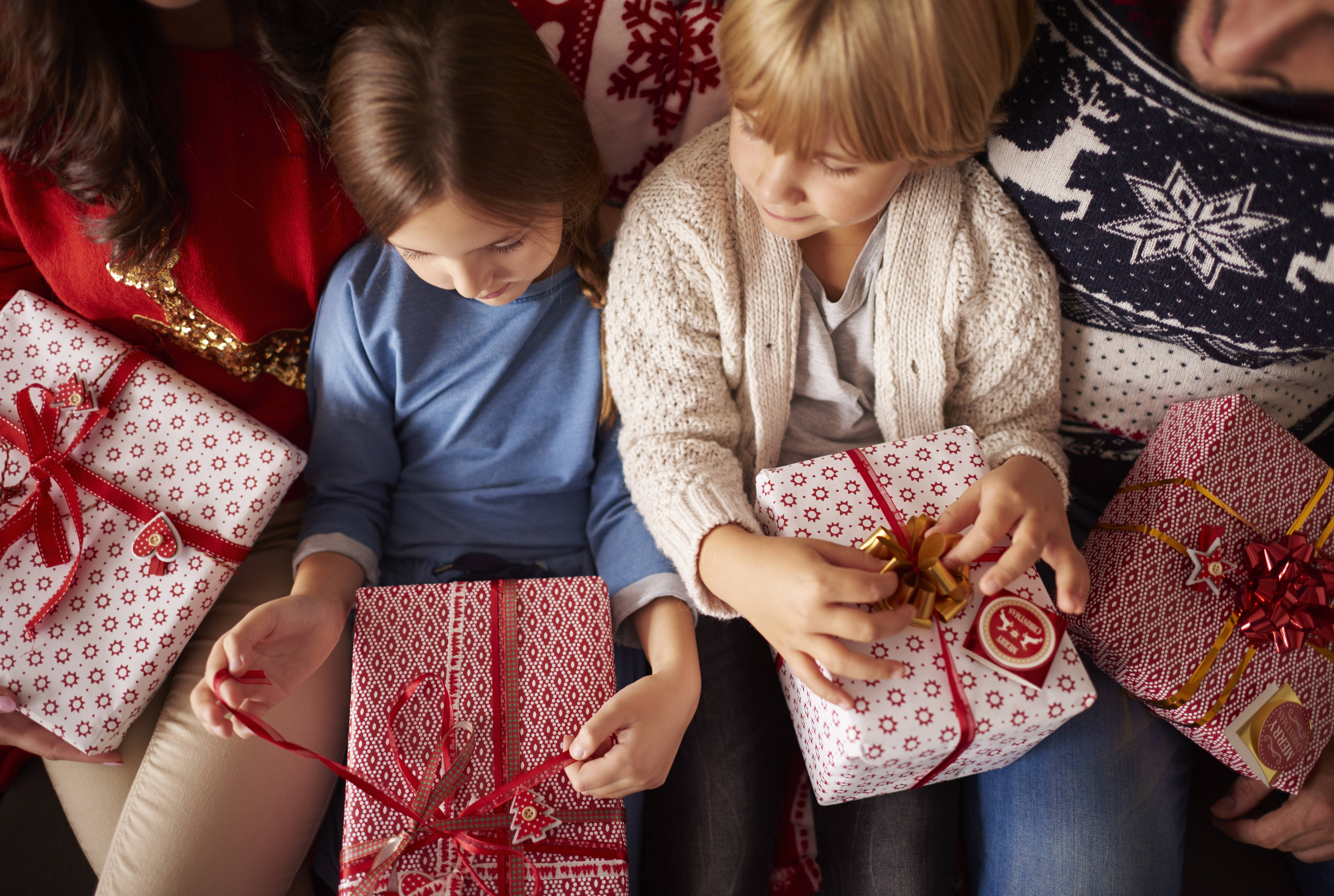 a couple of adults with children opening family Christmas presents and gifts