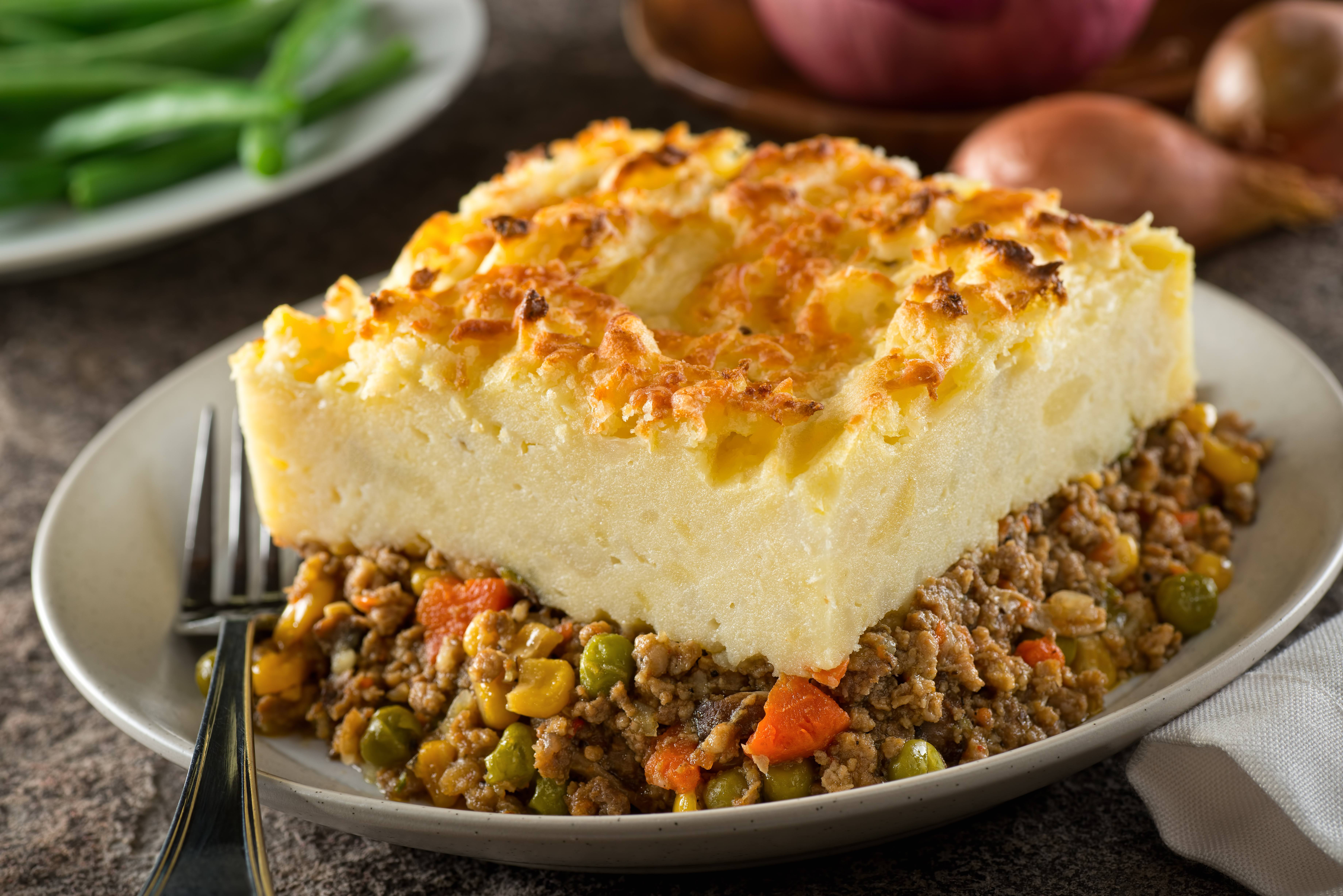 a slice of meat and potatoes Shepherd's pie on a plate with a fork