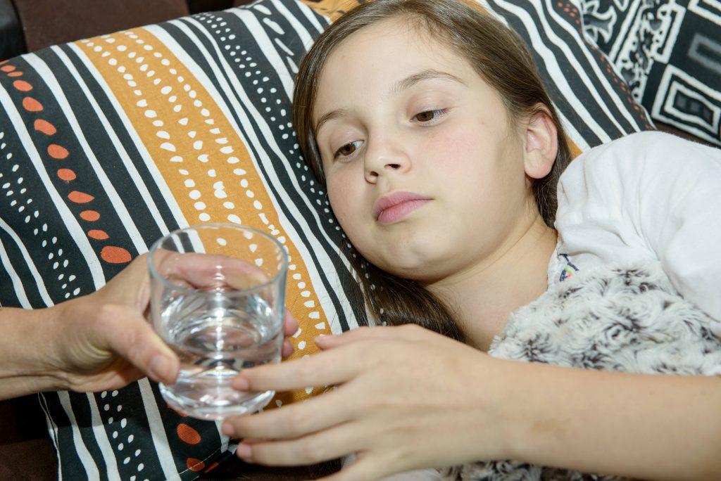 Una niñas enfermas beben un vaso de agua