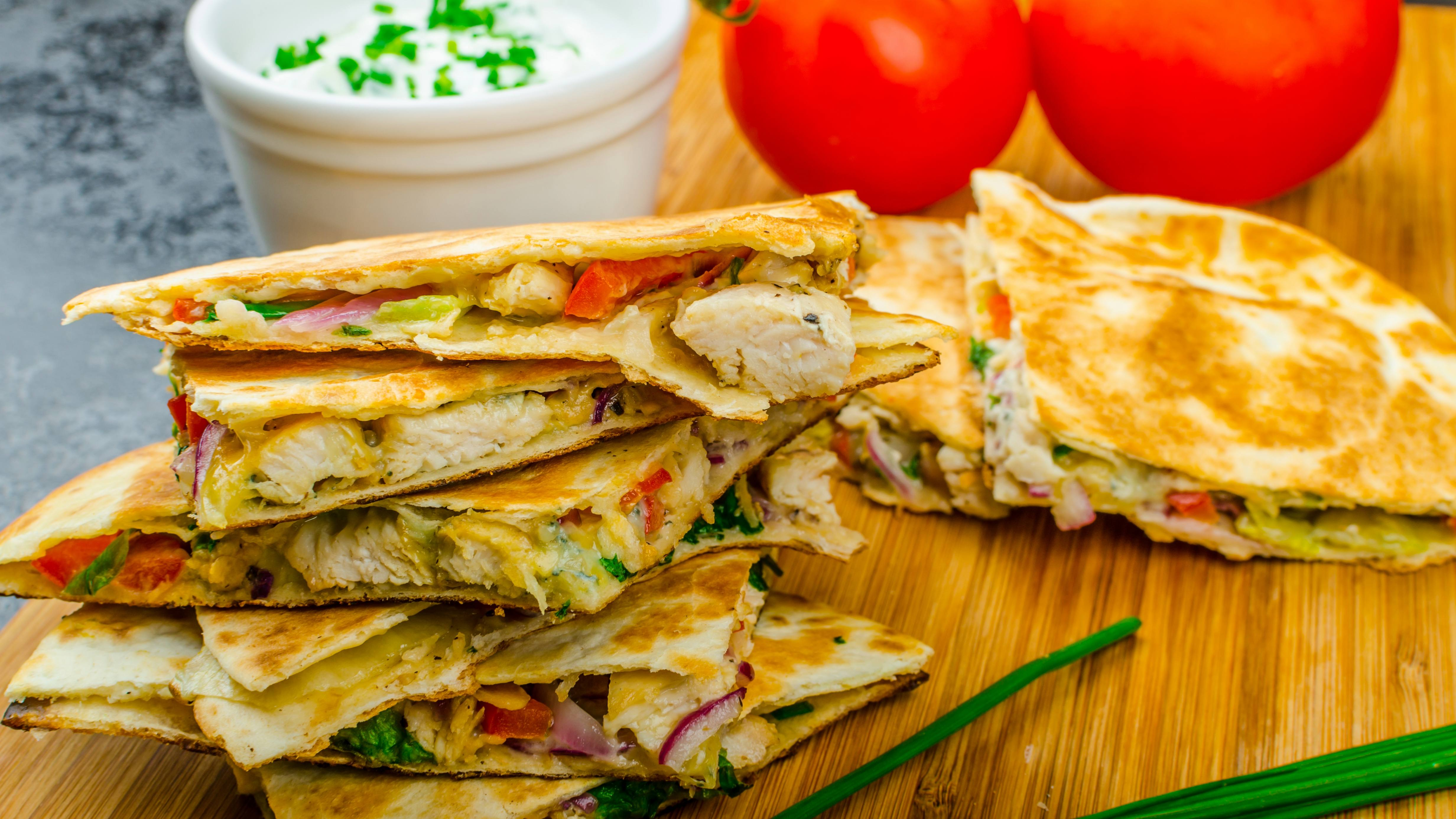 a chicken and vegetable quesadilla on a wooden plank