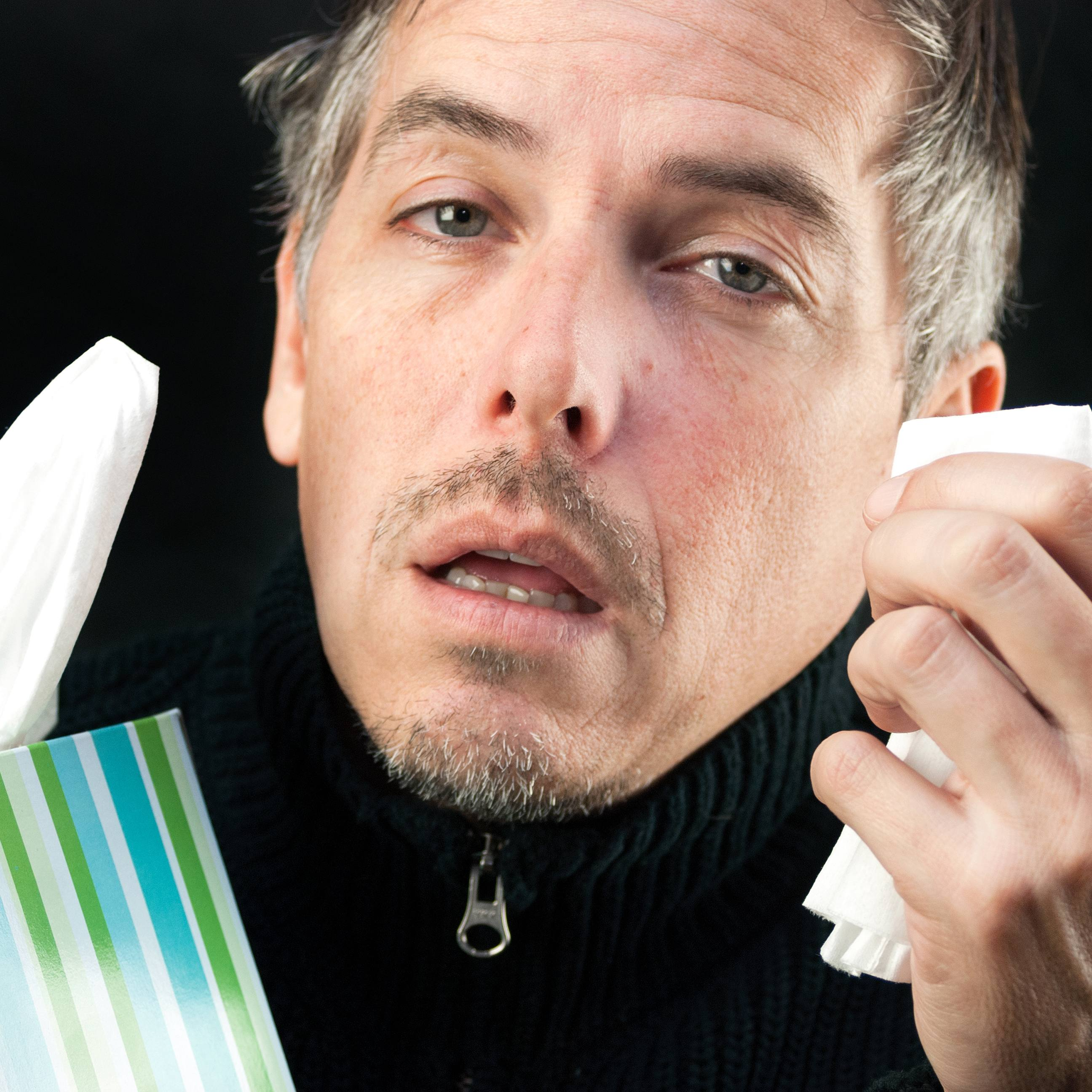 a close-up of a man looking sick with influenza or a cold, holding a tissue in one hand and a whole box in the other