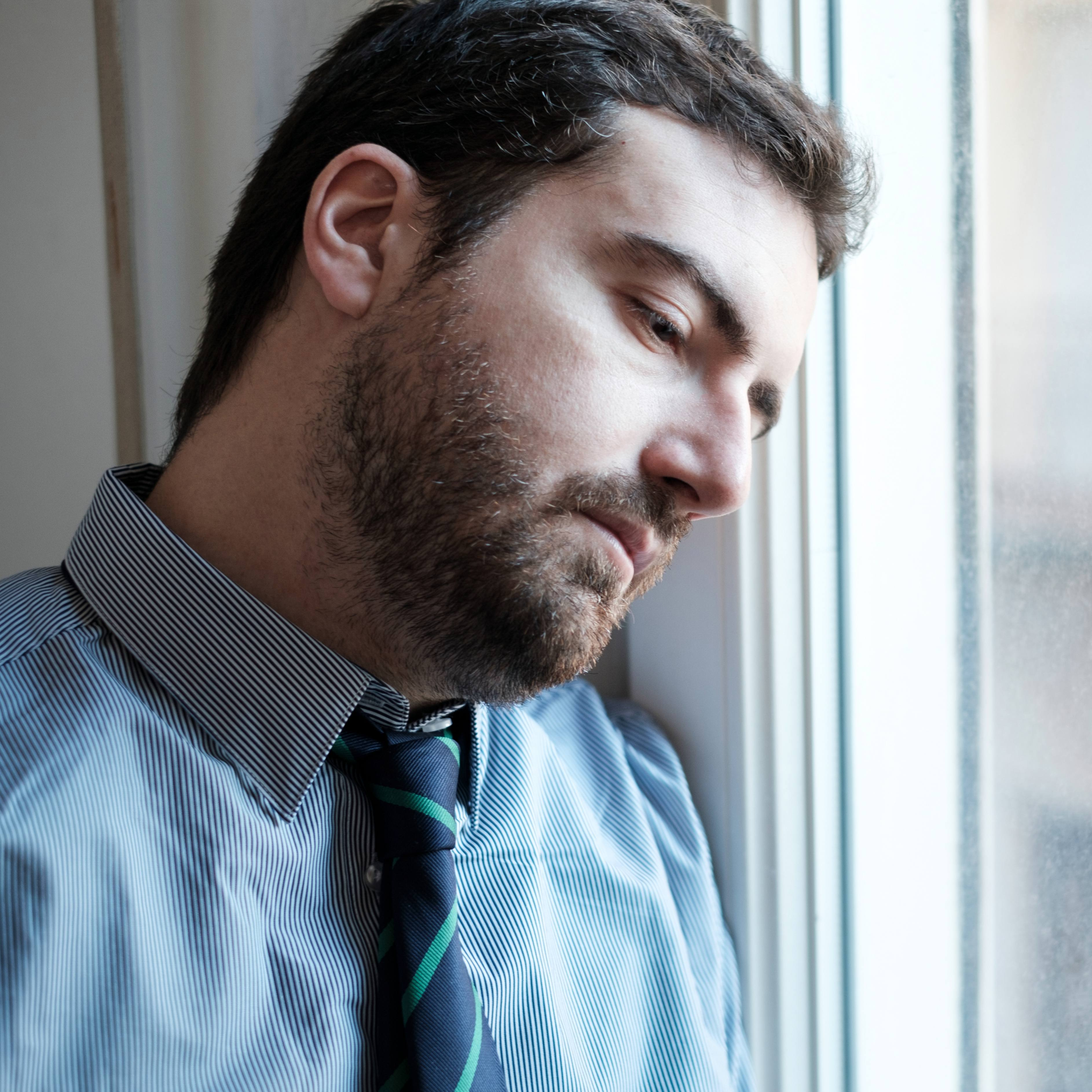 a young businessman looking sad and depressed out an office window
