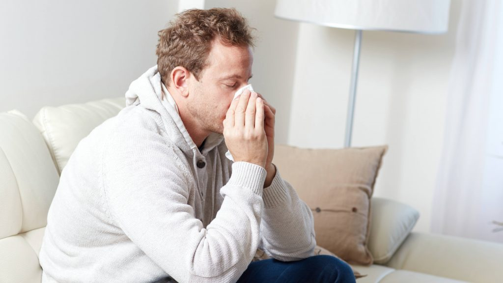 a young man sitting on a couch blowing his nose, with a cold, sinus allergies or a flu bug