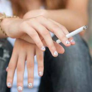 a young girl sitting a step, holding a cigarette and smoking