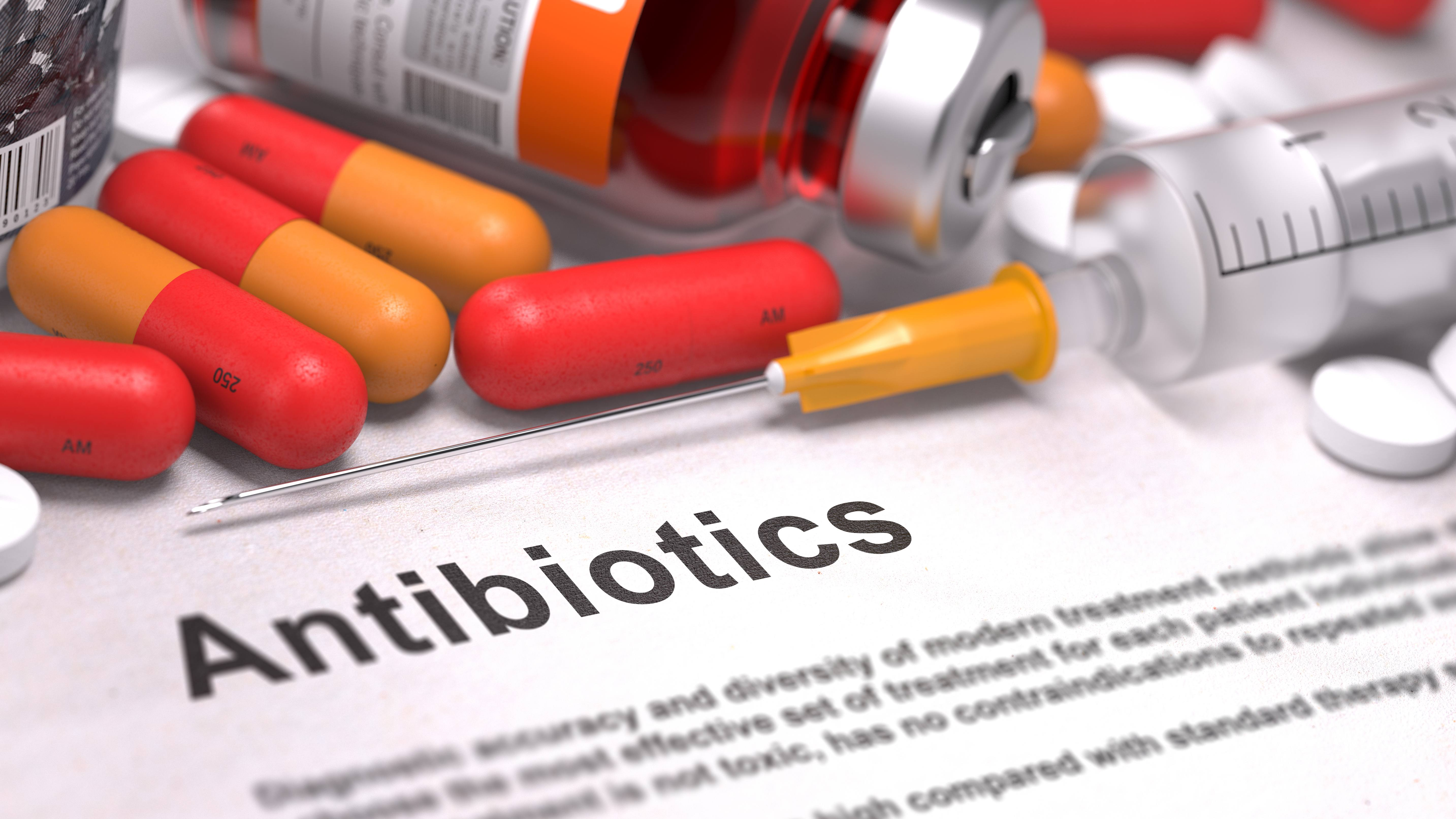 medication bottles, tablets, capules and a syringe spilled out on a piece of paper with the word Antibiotics written on it