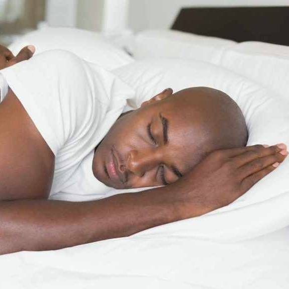 a man sleeping peacefully in bed, resting his head on a pillow