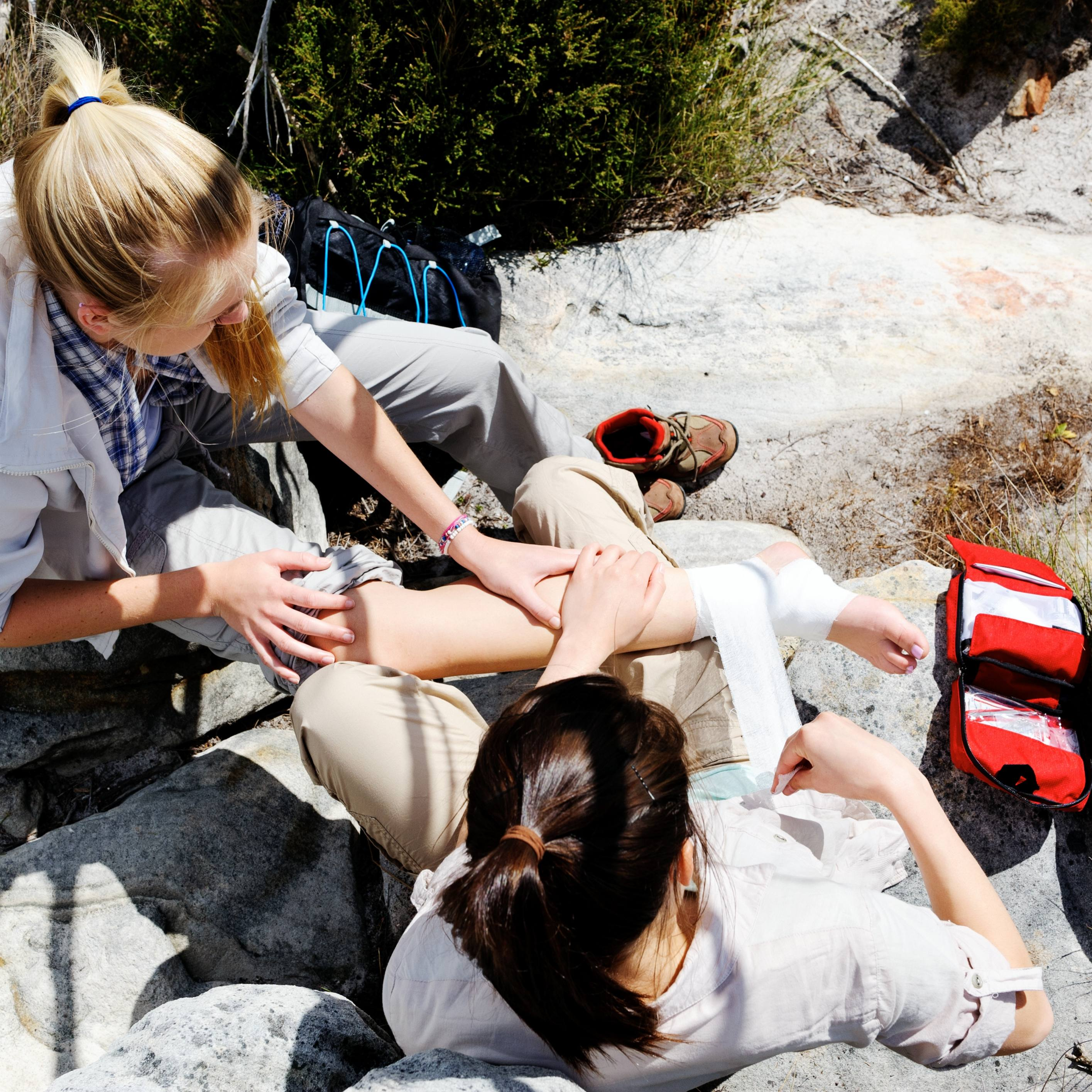 A woman has sprained her ankle while hiking, her friend uses the first aid kit to tend to the injury