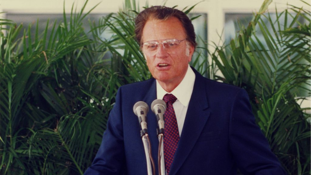 Billy Graham speaking in front of a podium with microphones