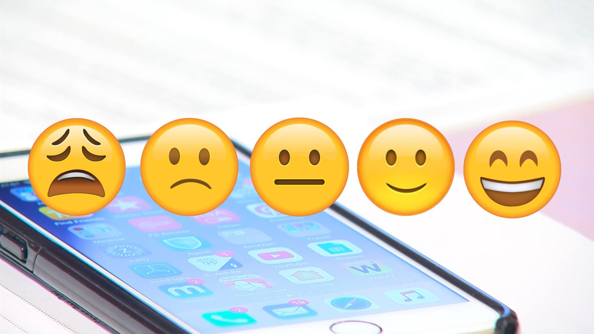 A screen shot of five emojis with a cell phone in the background.
