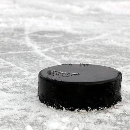 closeup of black hockey puck on the ice