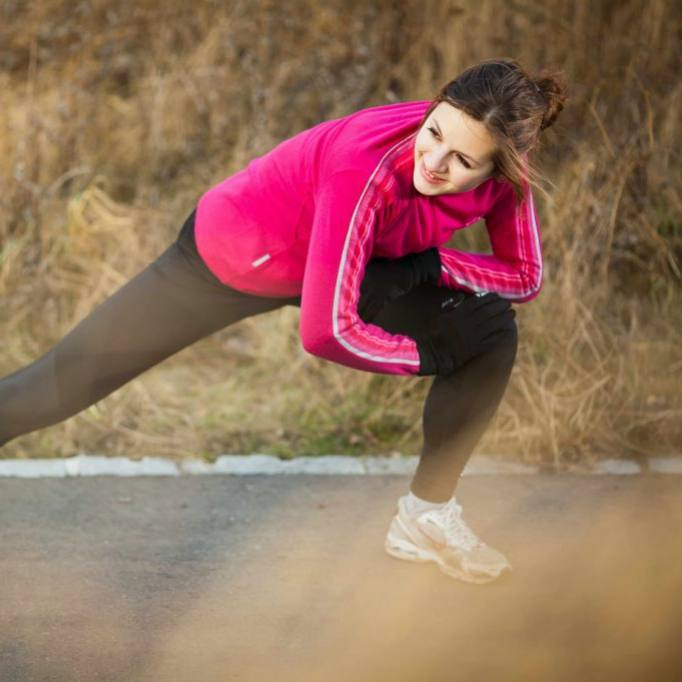 Young woman stretching during her run outdoors