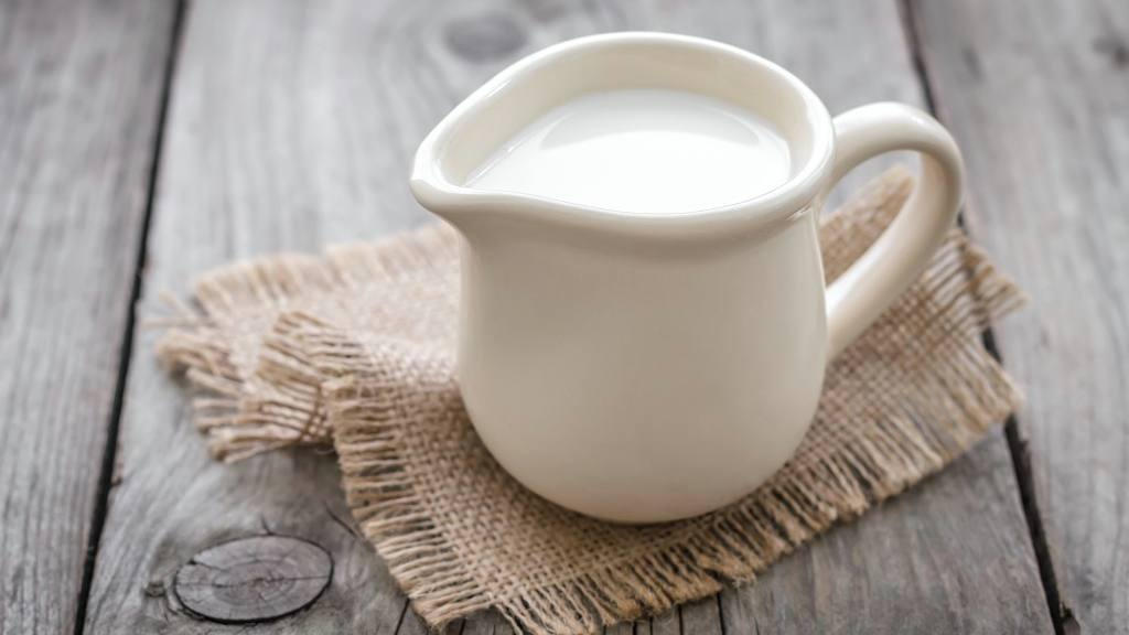 a small milk or cream pitcher sitting on a table, representing calcium intake
