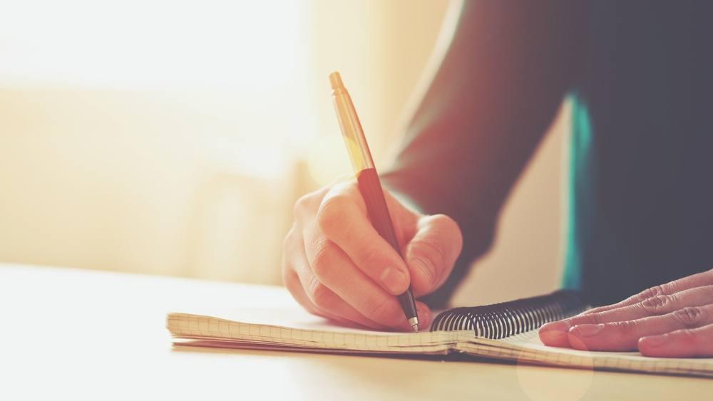 Unas manos femeninas sostiene un bolígrafo para escribir en una libreta