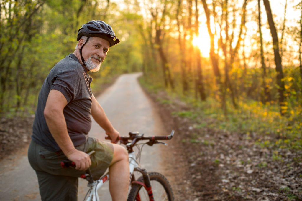 a smiling middle-aged man on a bike on a wooded bike path with the sun shining through the trees