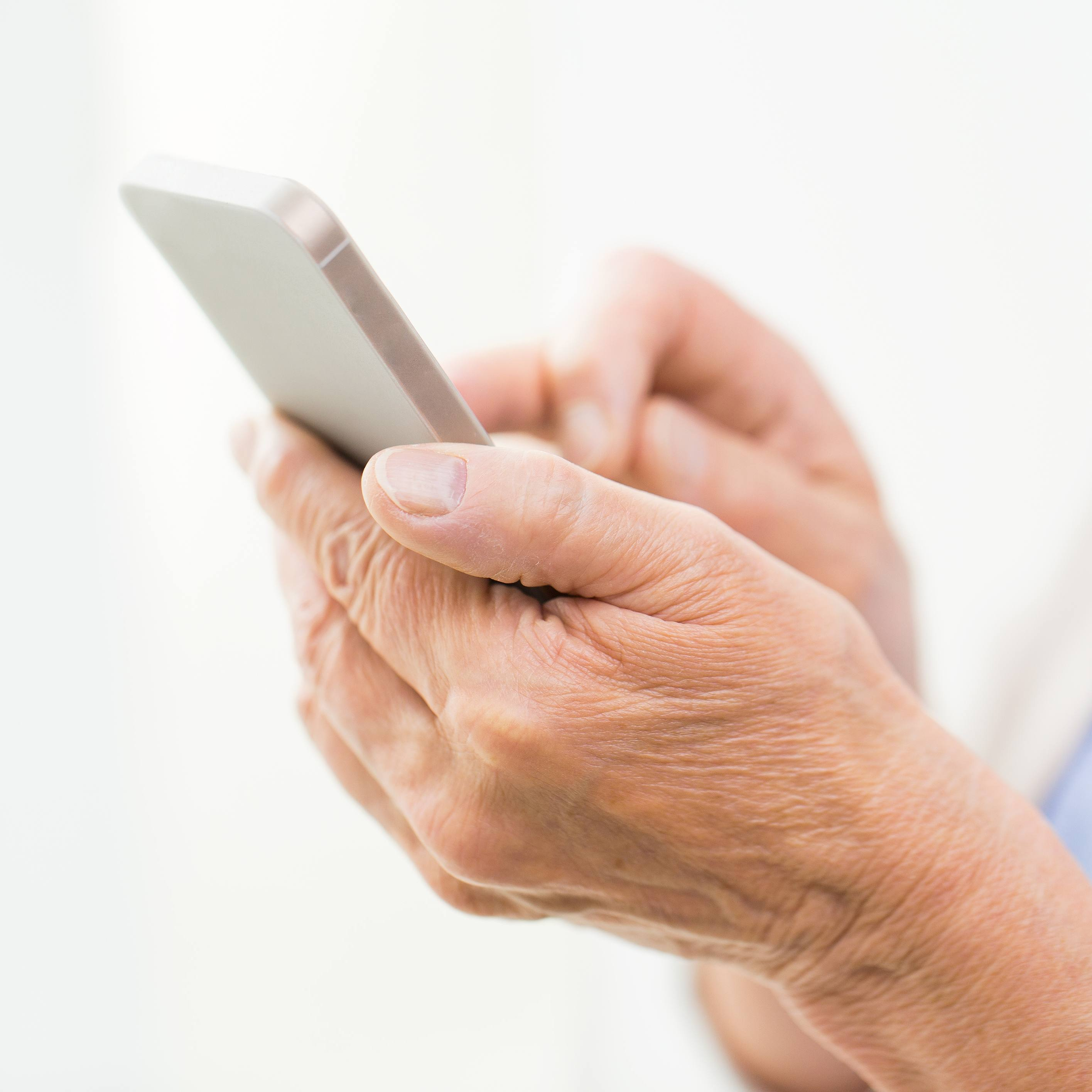 close up of senior woman hands with smartphone