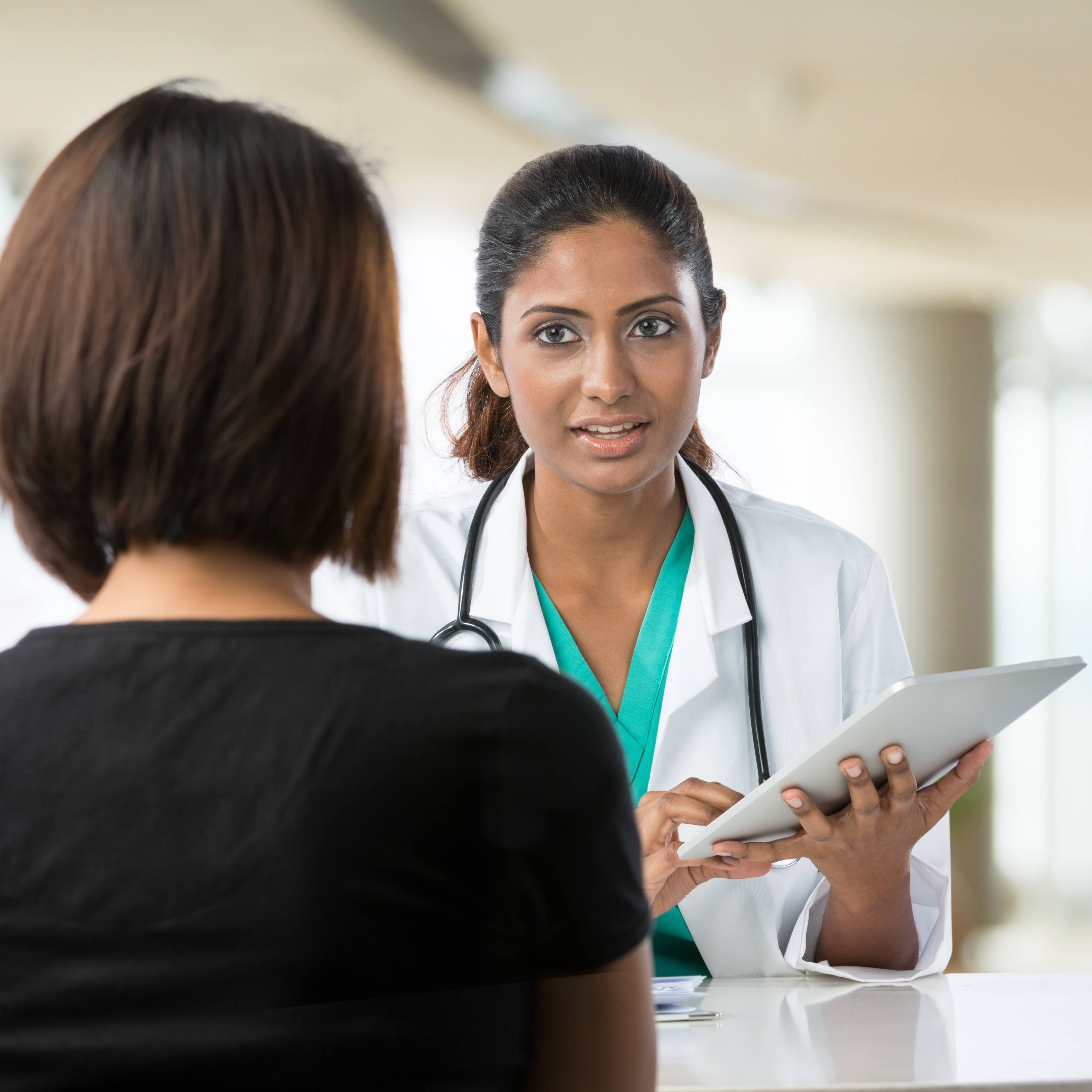 doctor talking with female patient in doctors office